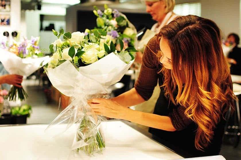 women decorating flower arrangement