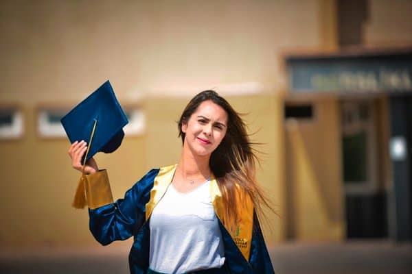 woman  wearing blue and yellow graduation toga