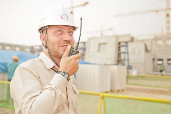 structural engineer wearing white hard hat holding two way radio