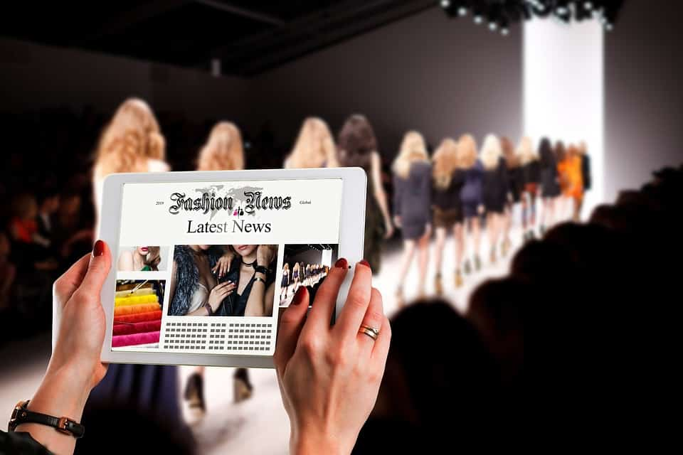 A person holding a tablet while watching a fashion show