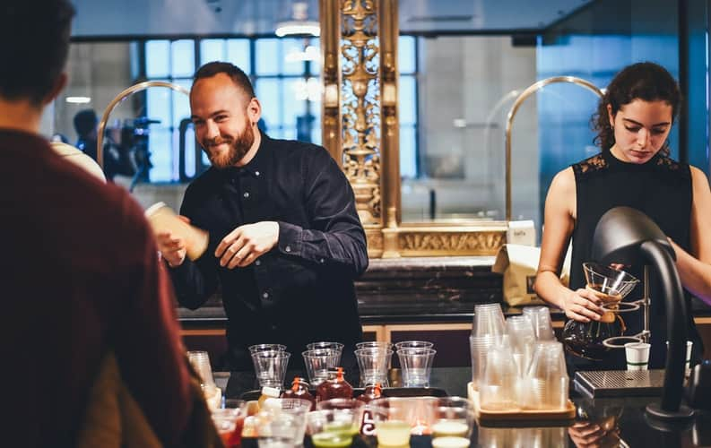 photo of man and woman mixing beverages