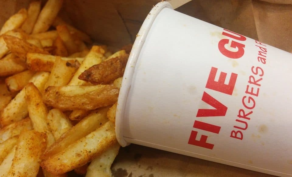 five guys fries pouring out of a cup
